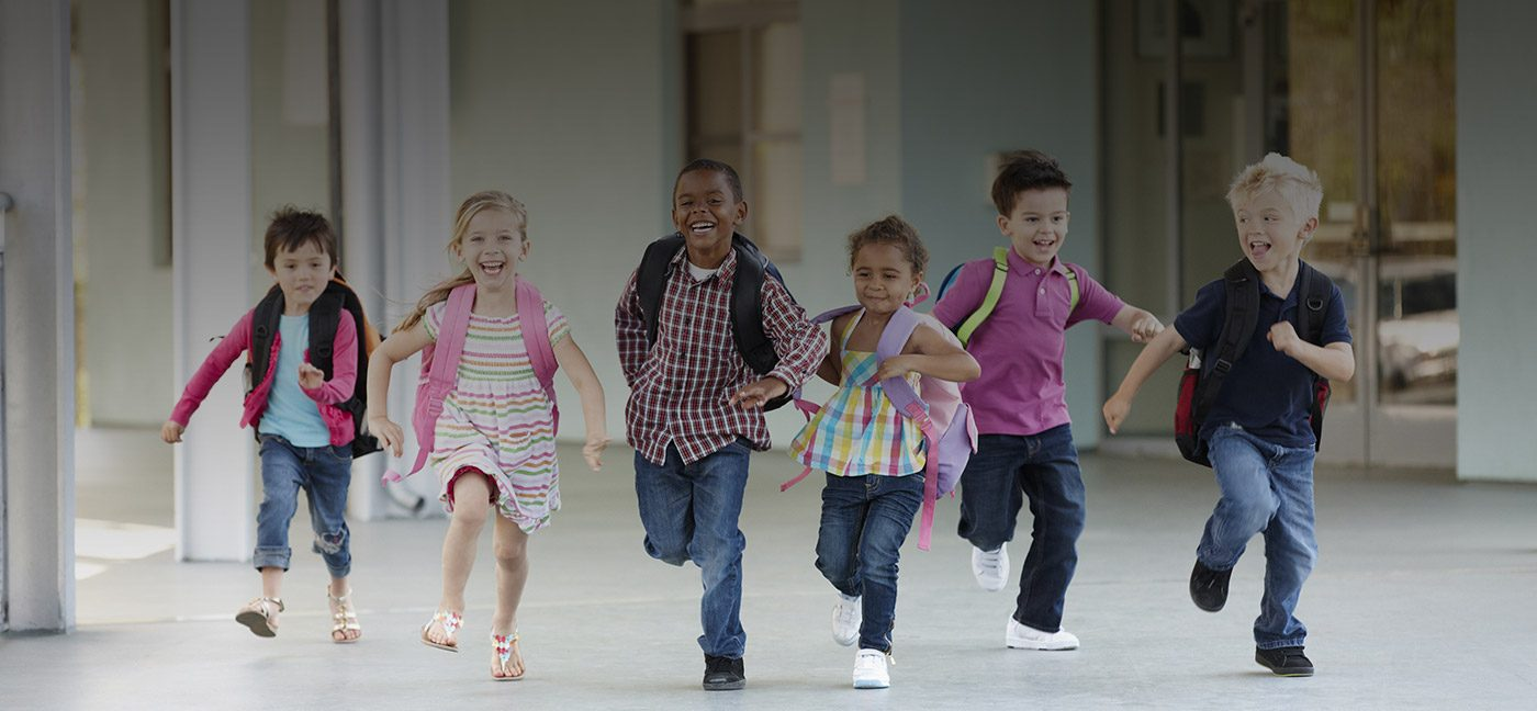 Group of young children running from school