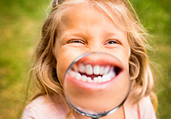 Little girl holding magnifying glass to smile