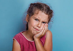 Little girl with toothache holding cheek