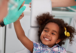 Little girl giving dentist hi five