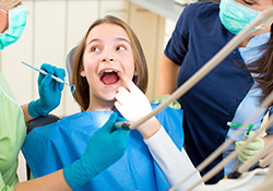 child in dental chair pointing to tooth